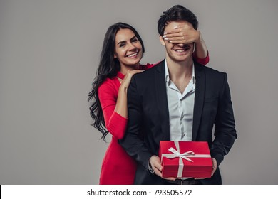Beautiful romantic couple isolated on grey background. Attractive young woman in red dress is making present for her handsome man in suit. Happy Saint Valentine's Day!