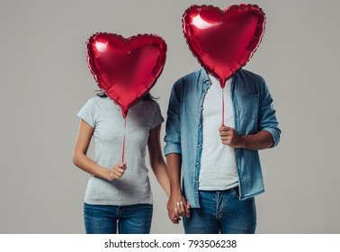 Beautiful romantic couple isolated on grey background. Holding hands with air balloon in shape of heart in hands. Happy Saint Valentine's Day!