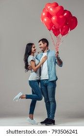 Beautiful romantic couple isolated on grey background. Attractive young woman and handsome man are hugging and smiling with air balloons in shape of heart in hands. Happy Saint Valentine's Day!