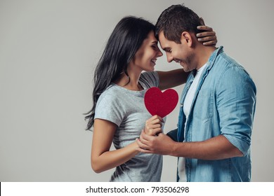 Beautiful romantic couple isolated on grey background. Attractive young woman and handsome man are hugging with red heart in hands. Happy Saint Valentine's Day!