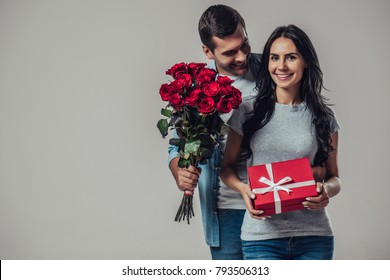 Beautiful romantic couple isolated on grey background. Attractive young woman and handsome man are standing with gift box and red roses in hands. Happy Saint Valentine's Day!