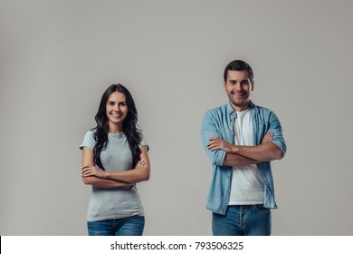 Beautiful romantic couple isolated on grey background. Standing apart from each other with hands crossed, smiling and looking at camera.