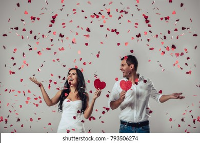 Beautiful romantic couple in love isolated on grey background with many little red flying hearts. Happy Saint Valentine's Day!