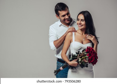 Beautiful romantic couple in love isolated on grey background. Handsome man is wearing necklace on his attractive young woman. Happy Saint Valentine's Day!
