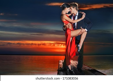 Beautiful romantic couple in tango pose against sunset background.