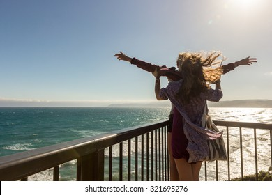 Beautiful Romantic couple tourist having fun laughing in funny titanic pose on terrace at sea. Happy man and woman holding together on travel vacation holidays on open ocean sea.