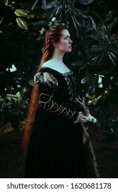 beautiful and romantic dark gothic red head witch in Historical elizabethan dress holding a skull