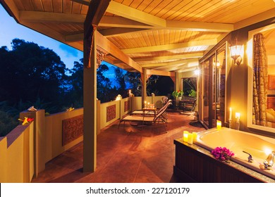 Beautiful Romantic Deck on Tropical Home with Bathtub, Candles, and Flowers at Sunset