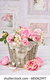 beautiful romantic flower decoration with pink roses and peonies in wicker basket in vintage style interior