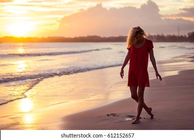 Beautiful romantic girl blonde in a red dress on the ocean shore during sunset. Silhouette of a girl on a sunset background near the ocean. Beautiful girl on the beach in a red dress.