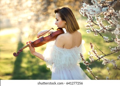 Beautiful romantic girl with dark hair and white dress playing on a violin in spring park. Sad violinist  from the back. Photo of sensual woman in glowing sun.Art work.