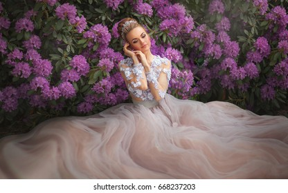 Beautiful Romantic Girl in fairy long lacy dress sitting near pink peonies.Gorgeous young model with perfect hair style and wreath accessories dreaming with close eyes in spring garden.Fantasy art