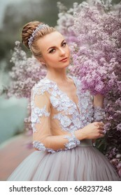 Beautiful Romantic Girl in fairy long lacy dress standing near pink peonies .Gorgeous young model with perfect hair style and wreath accessories looking at camera in spring garden.Arr work