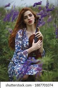 Schönes romantisches Mädchen mit rotem Haar und blauem Kleid, das Geige auf dem Naturfeld der Blumen hält. Foto von sinnlicher Frau. Kunstarbeit.