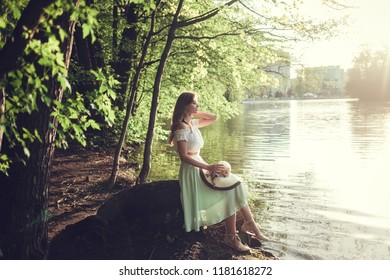 Beautiful romantic girl in vintage dress and hat sitting near river.