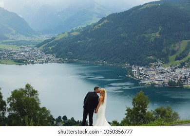 Beautiful romantic married couple kissing landscape lake and mountains background