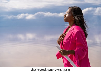 Beautiful romantic mixed race woman with closed eyes in pink suit. senses, meditation, enjoying nature. Romantic expression of dream subconscious. Looking for love, hope and life balance theme.