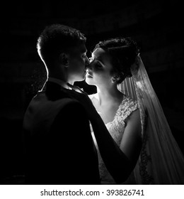Beautiful romantic newlyweds kissing b&w