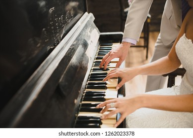 beautiful and romantic picture: the groom and the bride play together on the piano