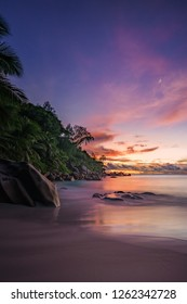 Beautiful romantic red sky after the sunset on paradise beach on the seychelles with granite rocks, palm trees and white sand.