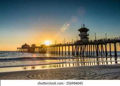 A beautiful romantic sunset on the pier overlooking a the ocean sand at sunset. Huntington Beach Pier wide shot during a bright blue and orange sunset with circles in the sand.
