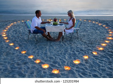 beautiful romantic supper with candles heart on the sand sea beach - a couple of newlyweds or lovers