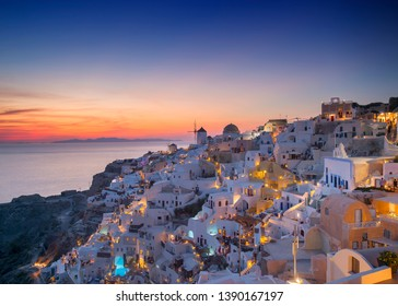 Beautiful romantic view of fabulous picturesque village of Oia with traditional white houses and windmills in Santorini island at Sunset, Greece