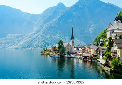 Beautiful romantic view on Church in Hallstatt on Hallstatter lake with boats, alps Mountains. Salzkammergut, Salzburger Land, nearby Salzburg, Austria.