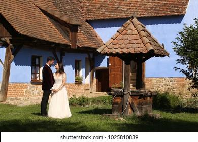 Beautiful romantic wedding couple of newlyweds hugging near old house