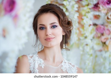 Beautiful romantic young woman in elegant dress posing on a background of flowers. Inspiration of spring and summer. Perfume, cosmetics concept.