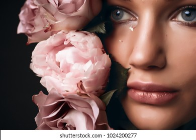 Beautiful romantic young woman in a wreath of flowers posing on a background of roses. Inspiration of spring and summer. Perfume, cosmetics concept.woman near the blossoming spring tree,eye lens