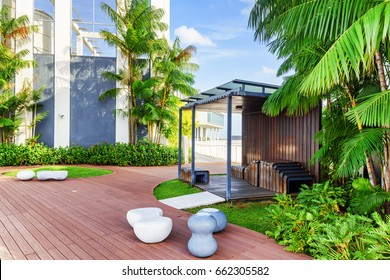 Beautiful rooftop garden. Outside terrace with amazing park. Modern wooden arbor among green trees. Urban eco design and mini-ecosystem. Landscaping in Singapore.