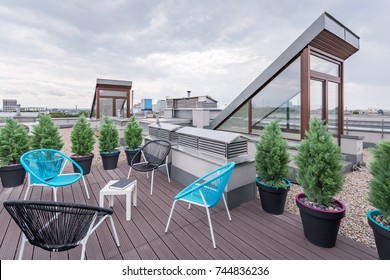 Beautiful rooftop terrace with modern black and turquoise chairs
