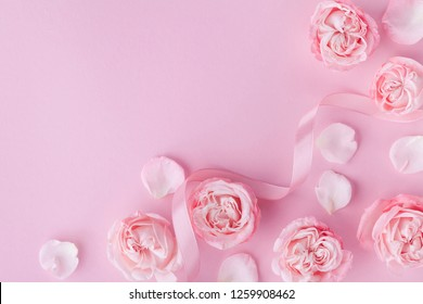 Beautiful rose flowers on pink background. Greeting card for Womens day or Mothers day. Flat lay.