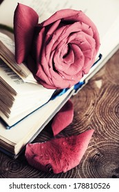 Beautiful rose and old books on wooden desk