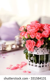 Beautiful rose in vase on table in room on bright background