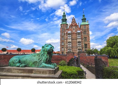 Beautiful Rosenborg Palace in Copenhagen, Denmark. Sculpture of lion against Rosenborg castle and blue sky. Statue is situated in front of bridge. Lion meditatively wistfully looking away.