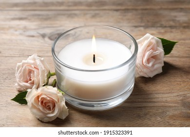 Beautiful roses near candle in glass holder on wooden table