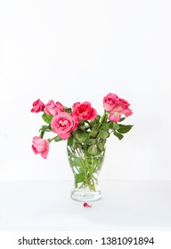 Beautiful roses in the transparent glass vase on white background