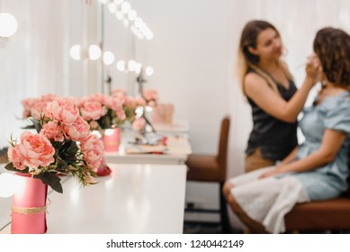 Beautiful roses in vase in beauty salon, female doing makeup on the background