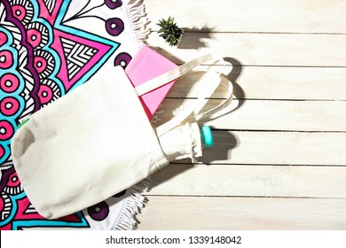 Beautiful round bright beach towel with mandala and white eco bag with book and bottle of water on wooden background. Top view, copy space. Concept beach, summer vacation.