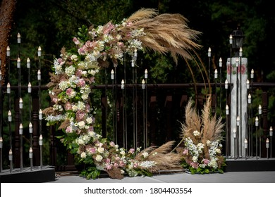 Beautiful round wedding arch decorated with flowers and greenery outdoors, copy space. Decorations for wedding ceremony in open air