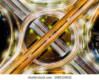 Beautiful roundabout intersection at night view with traffic movement. Aerial view of circle transportation in the city with colorful light. Drone view from night sky.