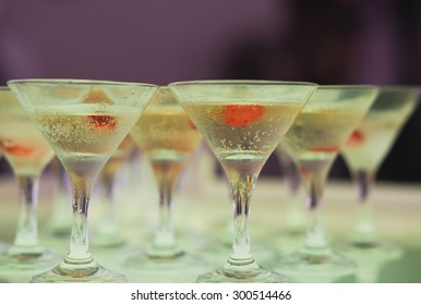Beautiful row line of different colored alcohol cocktails with mint on a open air party, tequila, martini, vodka, and others on decorated catering bouquet table on open air event, picture