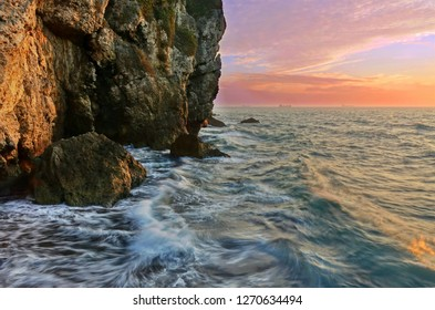 Beautiful rugged cliffs with waves and sunset sky and golden hour