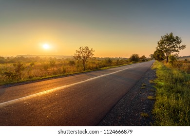 Beautiful rural asphalt road sunset landscape.