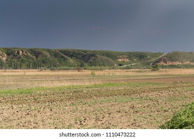 Beautiful rural landscape. Freshly plowed field and a number of hills in the distance.
