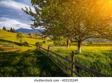 beautiful rural landscape with old wooden fence, mountain view on horizon and blue cloudy sky. natural summer background