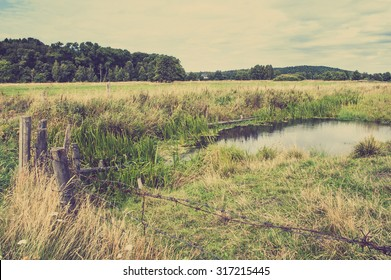 Beautiful rural landscape with pond surrounded by pasture and wooden fence, vintage photo.