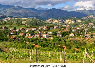 Beautiful rural scenery of Bulgarian wine region not far from Melnik, Bulgaria. Sandstone formations of Melnik Pyramids on background. Bulgarian mountain village landscape